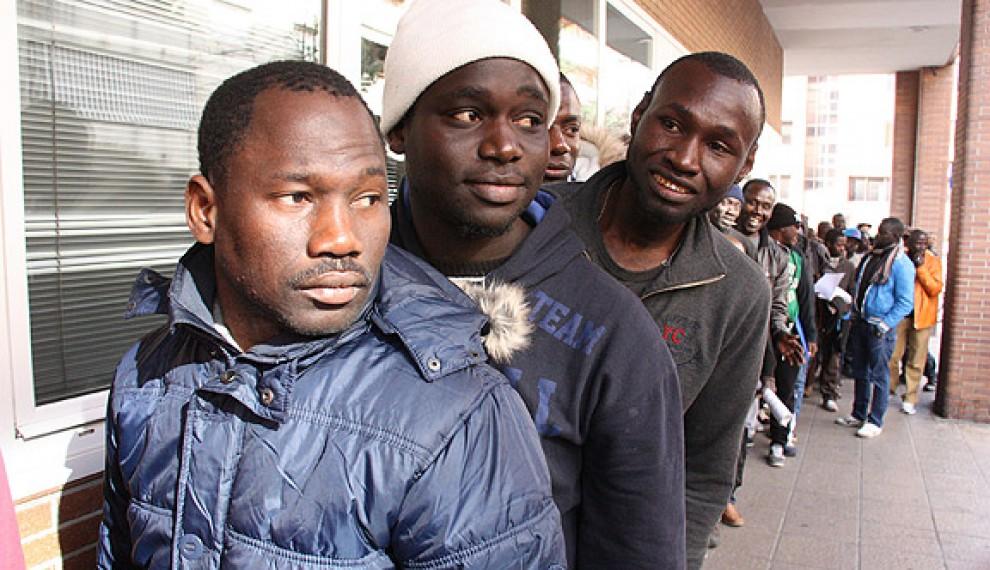 Immigrants fent cua davant d'una Oficina d'Atenció al Ciutadà per sol·licitar l'arrelament social.