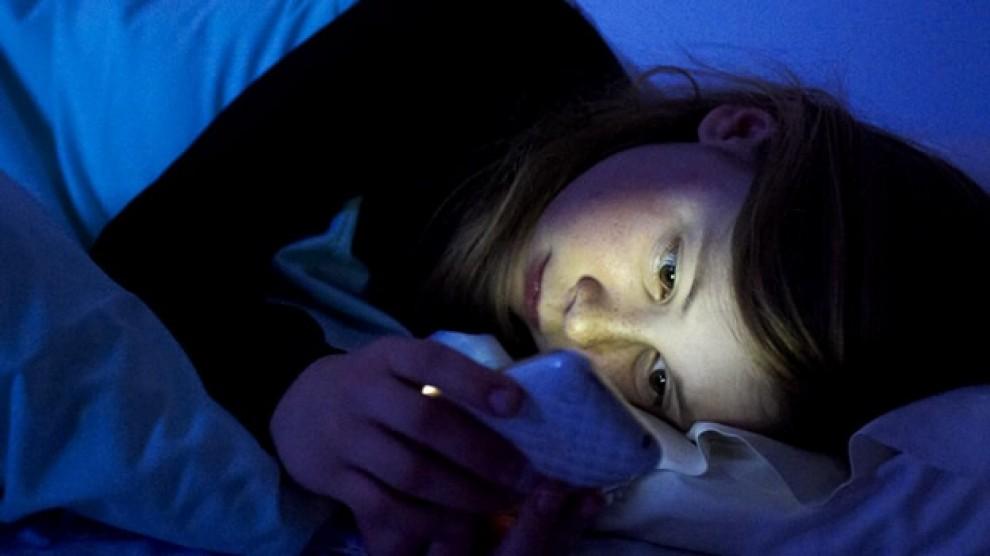 Un noia amb un mòbil, al llit