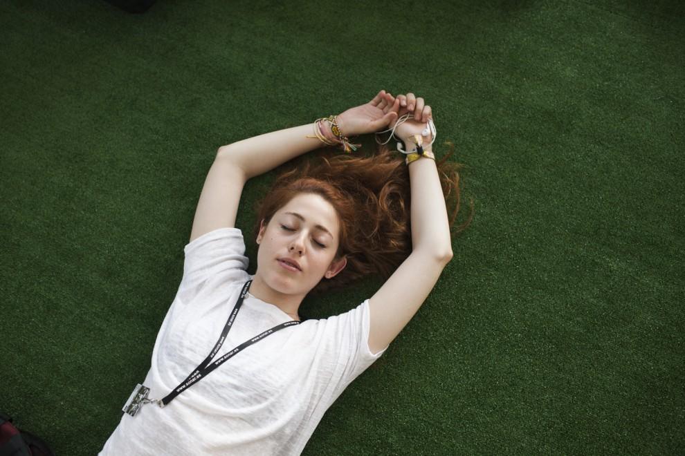 Una noia escoltant música estirada sobre la gespa