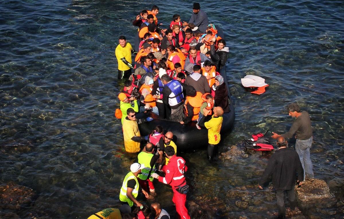 Ajudant a sortir gent d'una barca que ha arribat a una zona rocosa