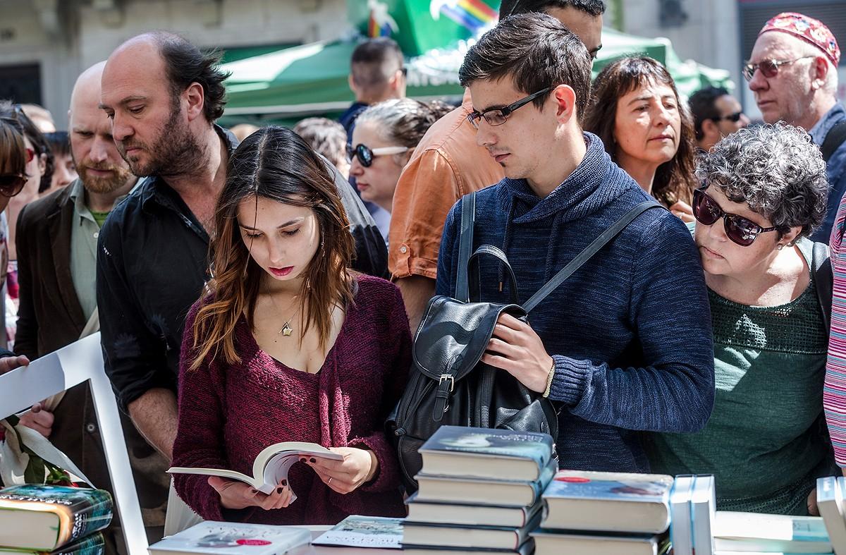 Una noia consulta un llibre aquest Sant Jordi en una paradeta a La Rambla