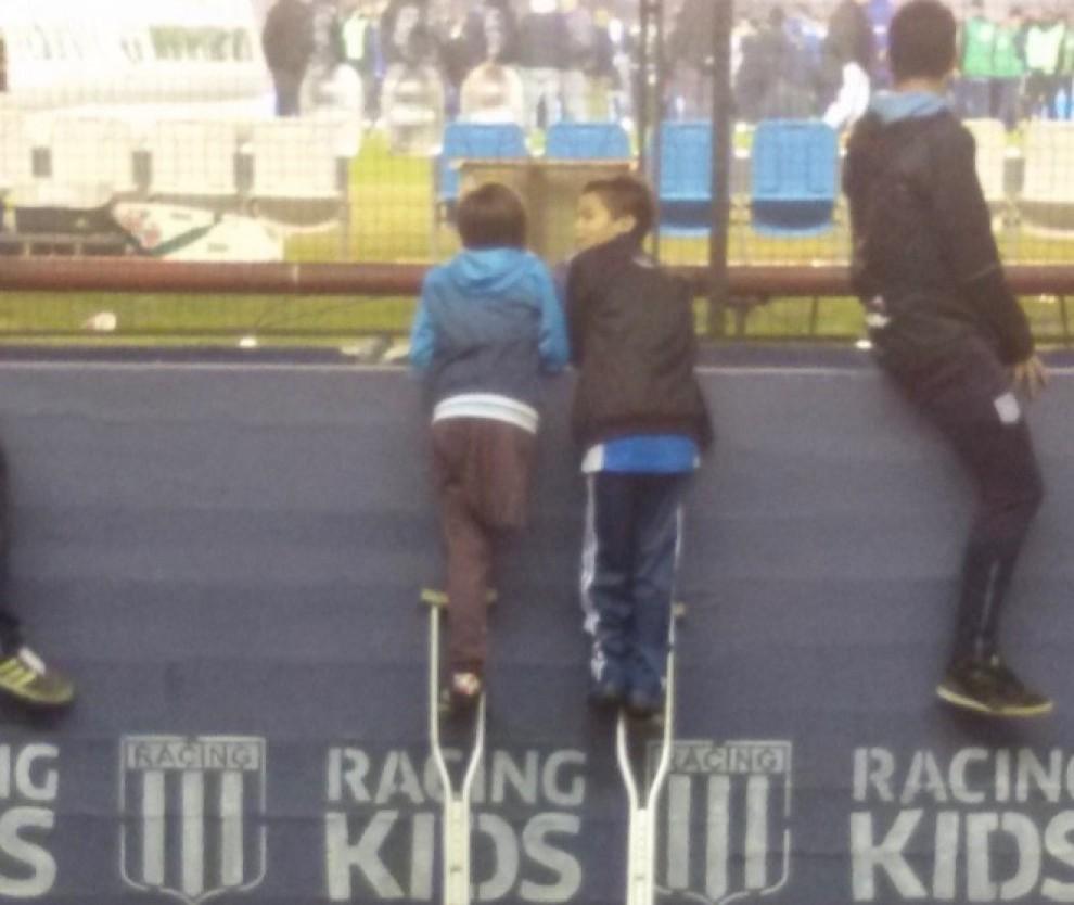 Santiago Fretes, a l'esquerra, mirant un partit de futbol a l'estadi del Racing Club d'Avellaneda d'Argentina, amb un amic seu