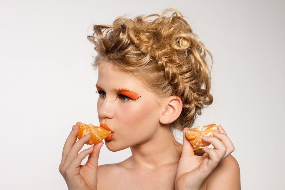 Una noia menjant una mandarina, una fruita rica en vitamina C