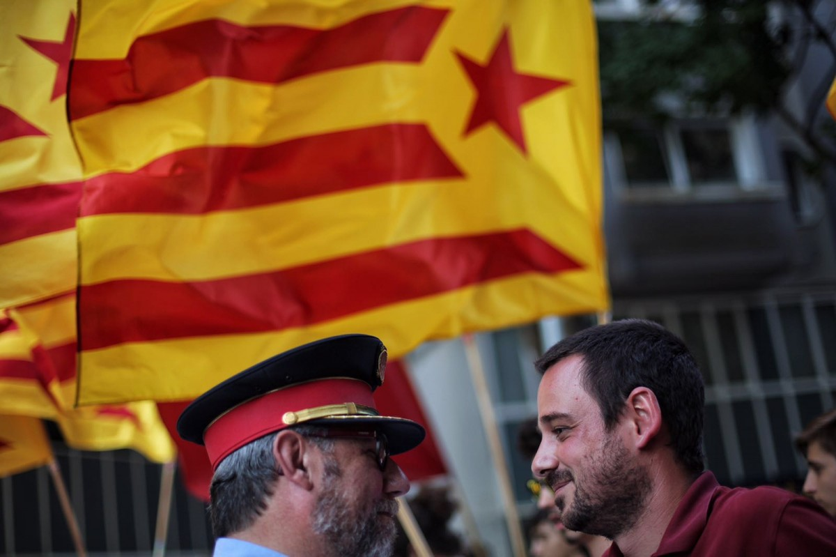 Lluc Salellas, regidor de la CUP a Girona, parlant amb un Mosso d'Esquadra
