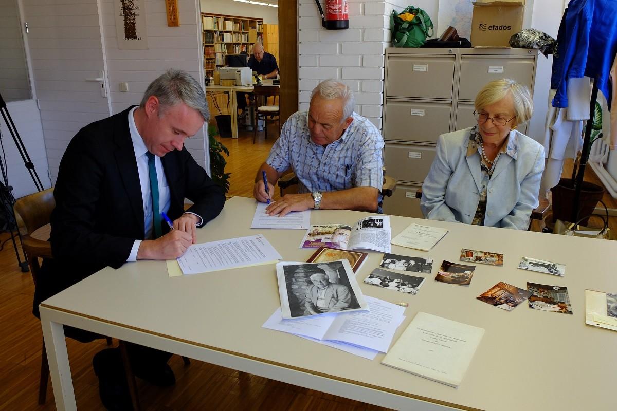 L'alcalde de Puigcerdà, Albert Piñeira i els cedents Josep Alujo i Monique Greiner, signant el document de cessió a l'Arxiu Comarcal de la Cerdanya