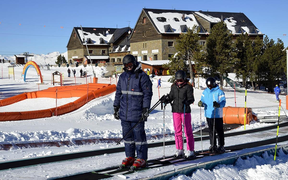 Tres esquiadors pugen per una cinta transportadora a l'estació d'esquí de Port Ainé