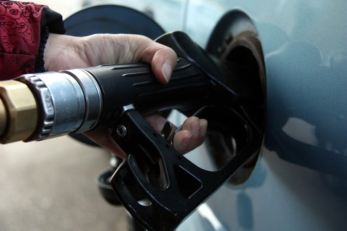 Una mà subjecta la mànega d'un assortidor de gasolina