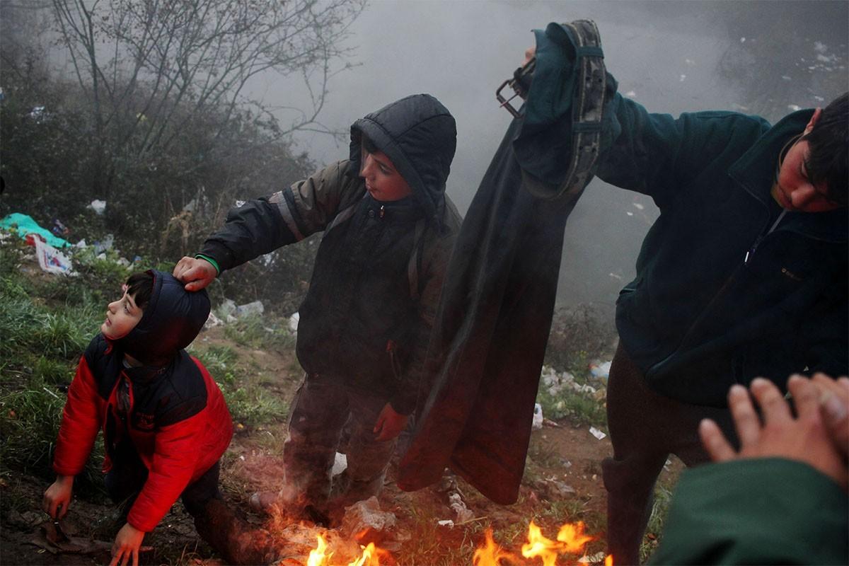 Uns nens sirians, escalfant-se a l'entorn del camp de refugiats d'Idomeni, a Grècia
