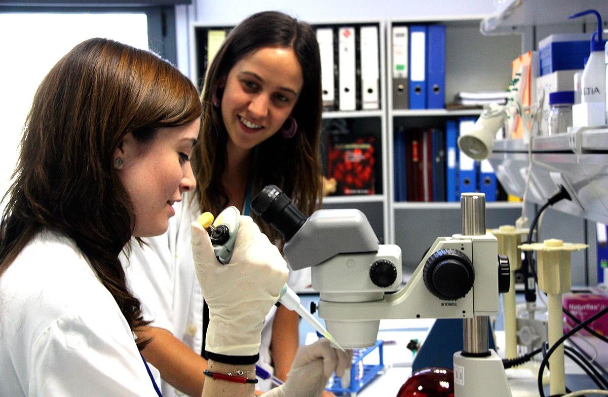 Dues dones científiques conversen en una laboratori