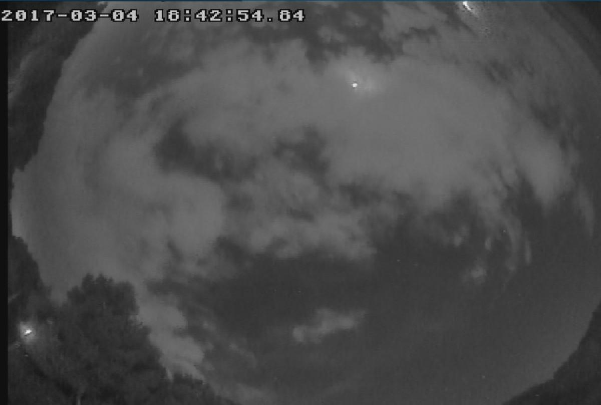 El bòlid, un meteor brillant, a l'extrem superior de la imatge.