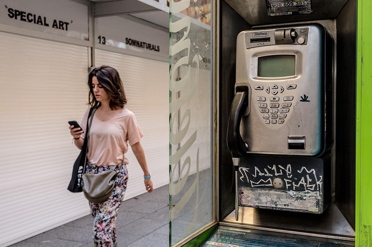 Un telèfon públic de Barcelona i una noia amb un telèfon mòbil