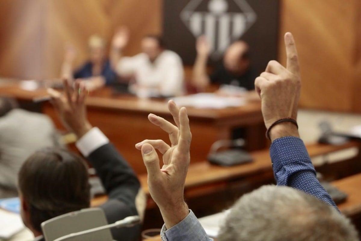 Mans alçades en votació en un ple.
