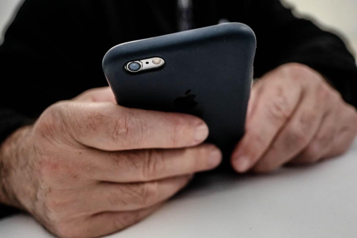Una persona consultant el seu telèfon mòbil