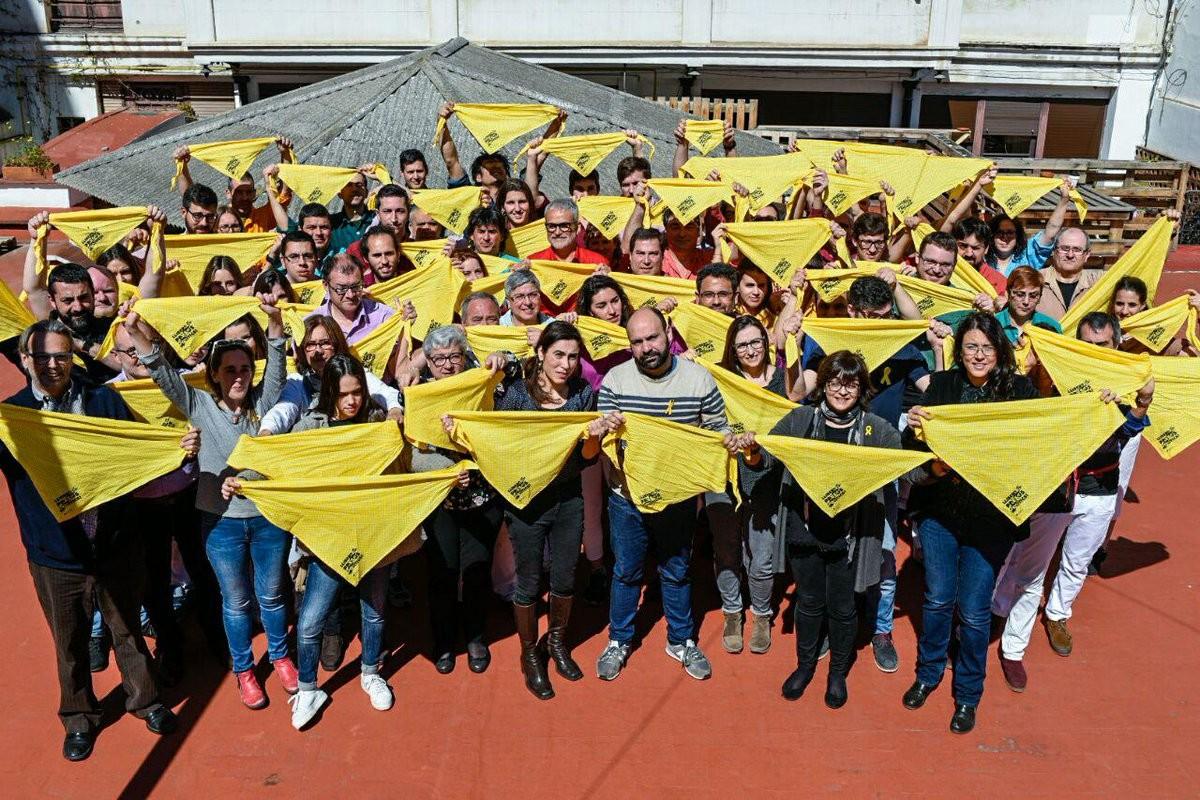 Castellers i membres d'Òmnium mostrant el mocador groc