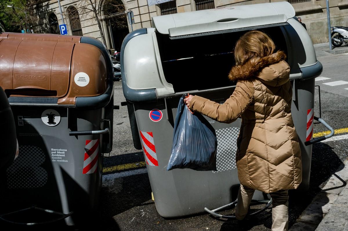 Una ciutadana llençant les escombraries al contenidor.