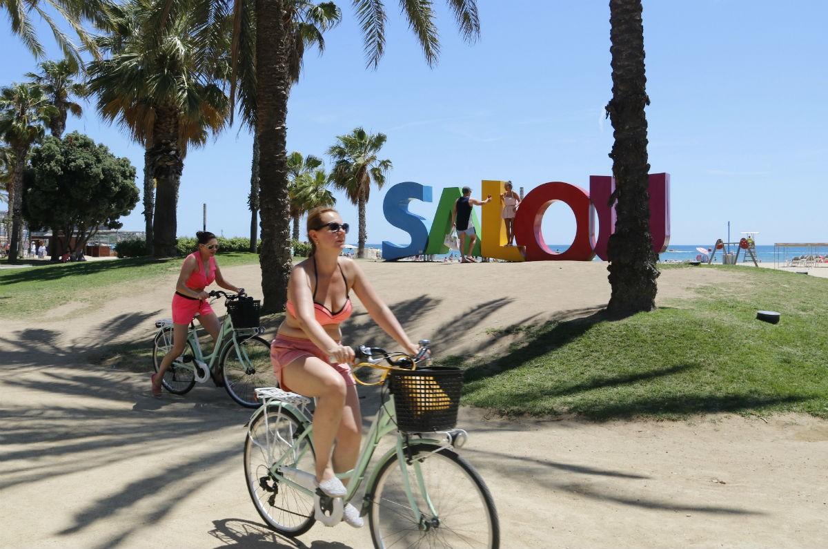 Diversos turistes que passegen en bicicleta per Salou