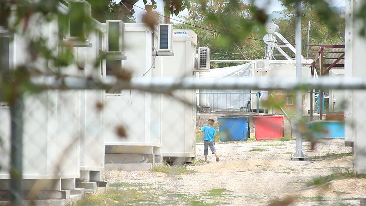 Un nen dins el camp juga a fet-i-amagar amb uns amics entre els contenidors on viuen