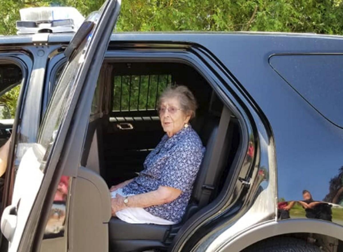 La Simone, asseguda al seient de darrere d'un cotxe patrulla
