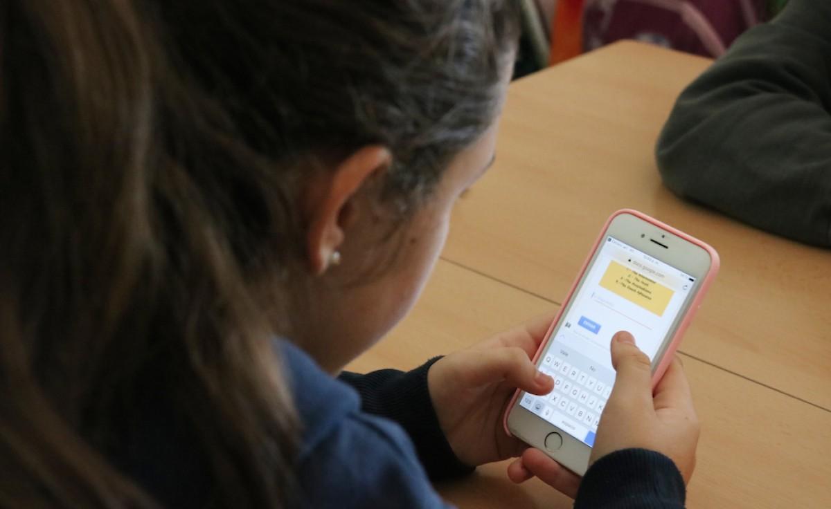 Una noia consulta el seu telèfon mòbil