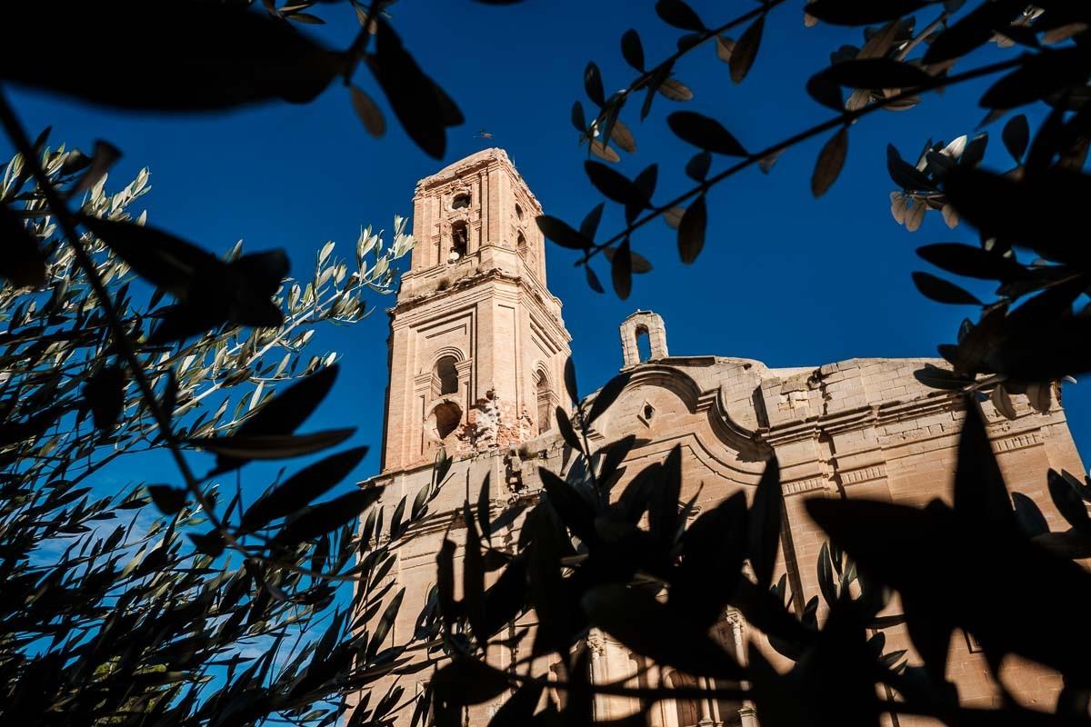 L'església del Poble Vell de Corbera d'Abre vista entre branques d'olivera