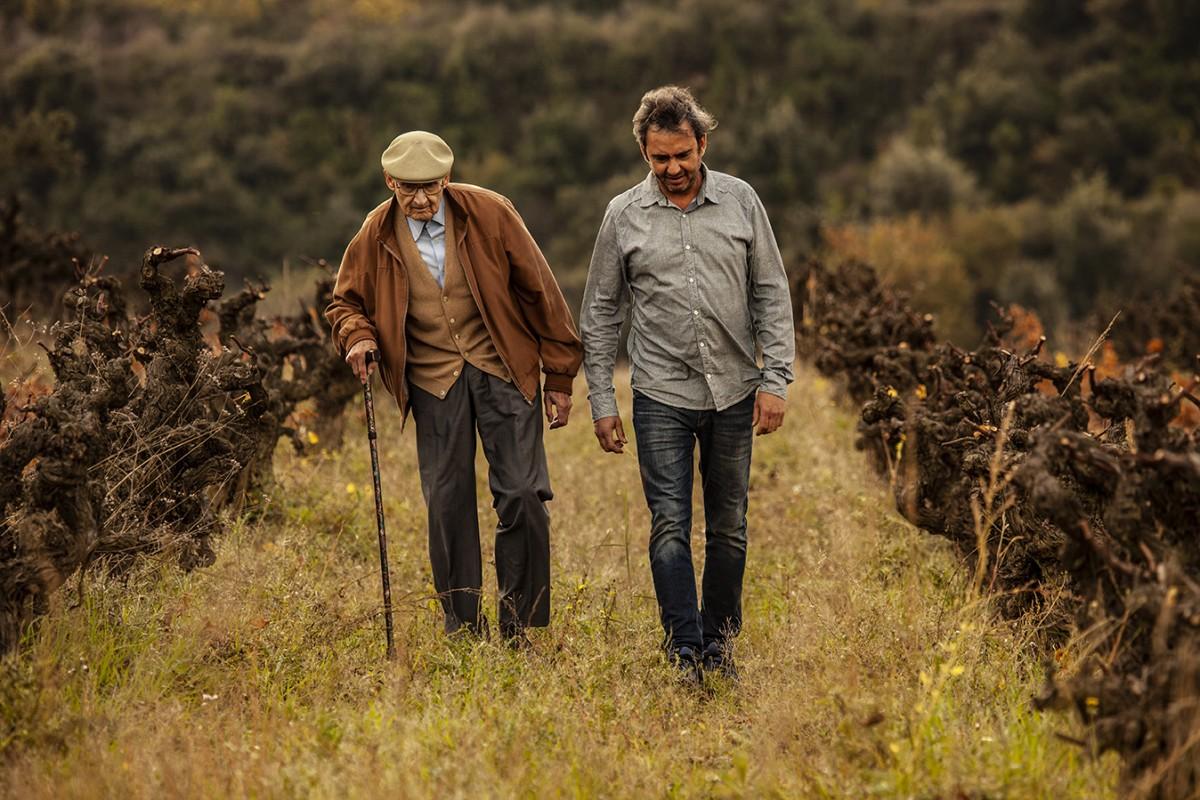 Pere Llopart i Vilarós i el seu fill Pere Llopart i Llopart; representants de la quarta i cinquena generació d'elaboradors de la família, passegen entre vinyes velles de muntanya de l'Heretat.
