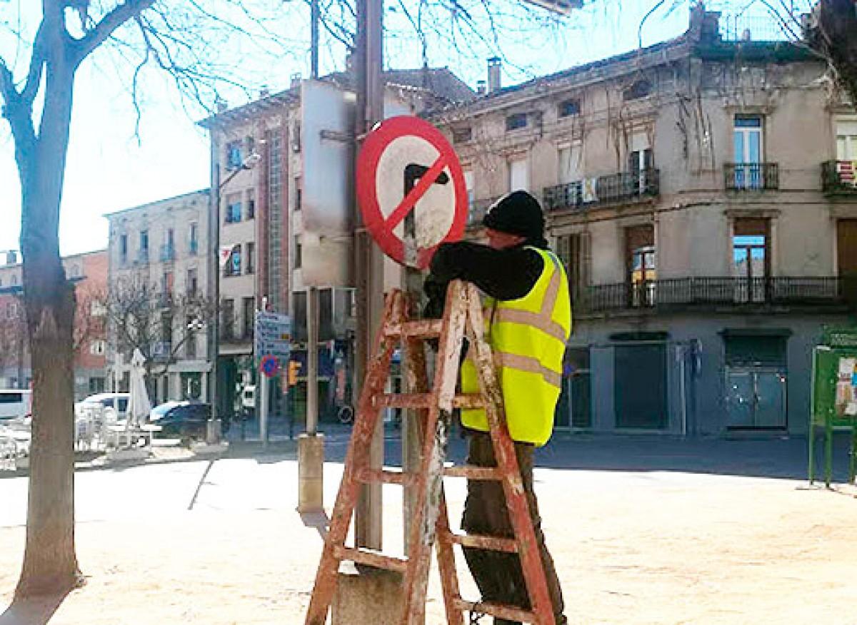 Un operari, netejant el mobiliari urbà