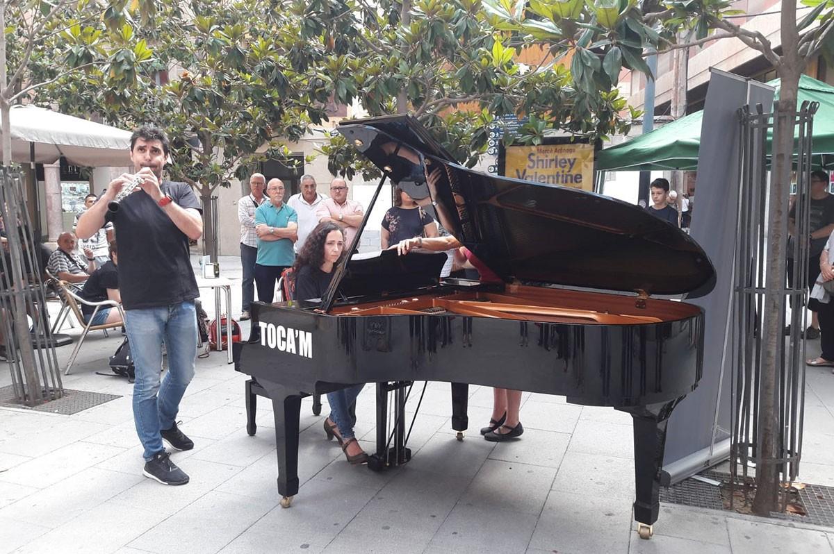 Una de les persones que s'ha atrevit a tocar el piano de cua instal·lat a la plaça de l'Àngel de Tortosa.