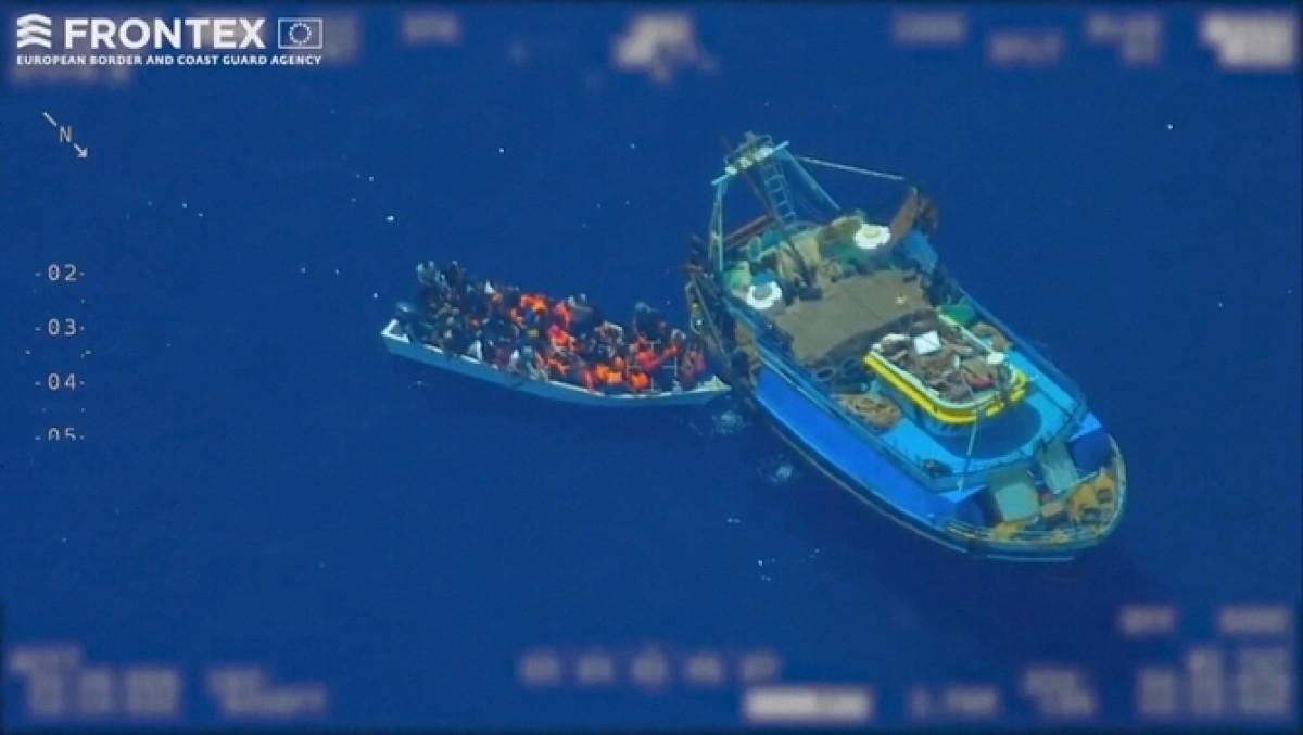 Imatge d'un pesquer amb un patera plena de persones migrants.