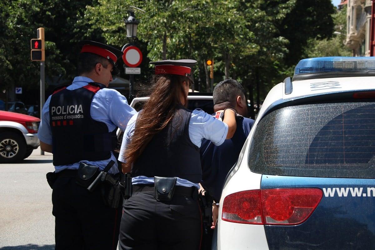 Dos agents dels Mossos detenint una persona.
