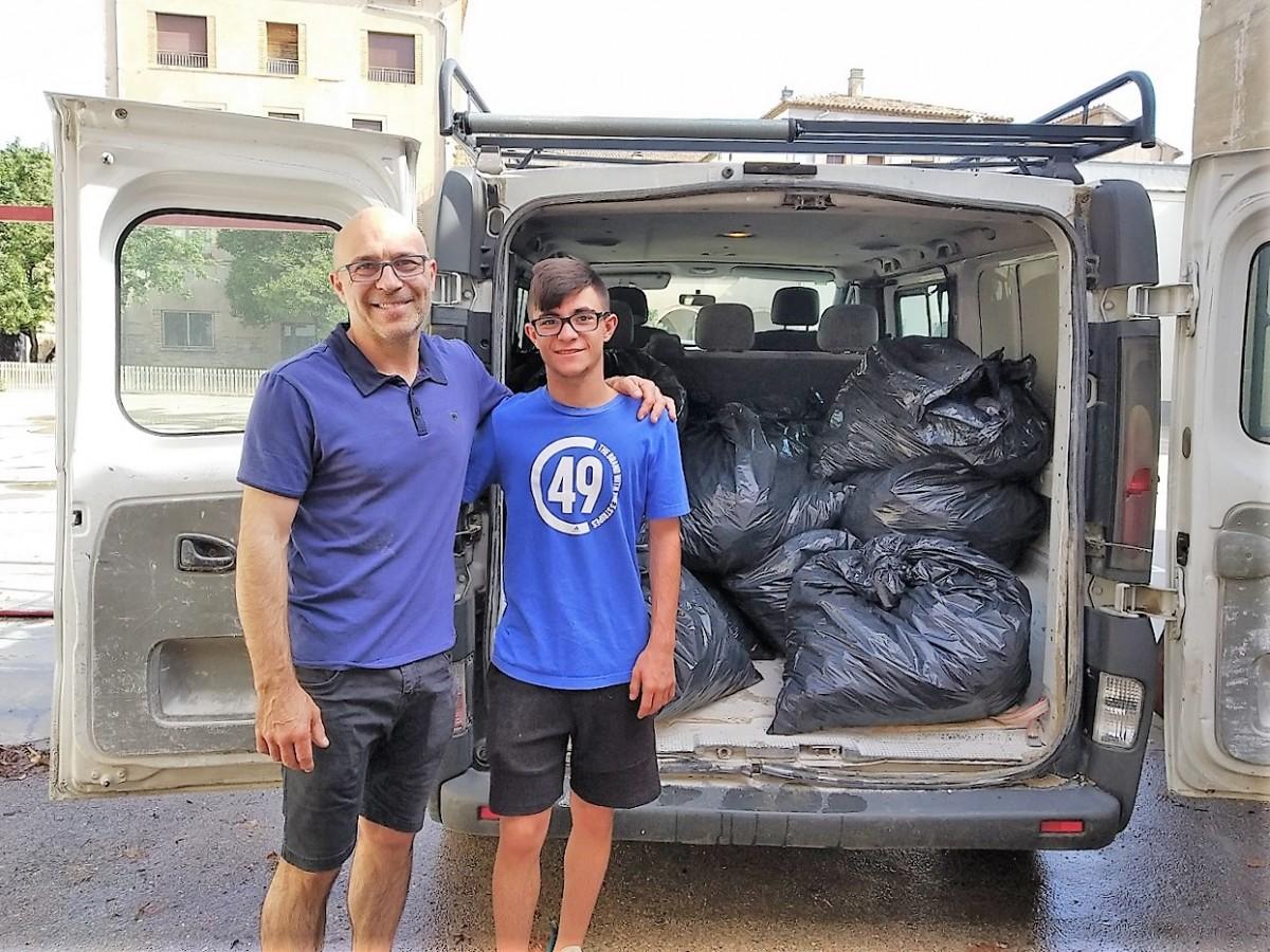 El Marc, amb el seu pare, recollint els taps de plàstic