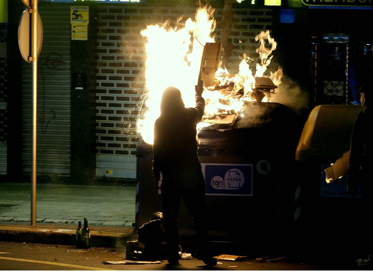 Un manifestant cremant un contenidor a Tarragona.