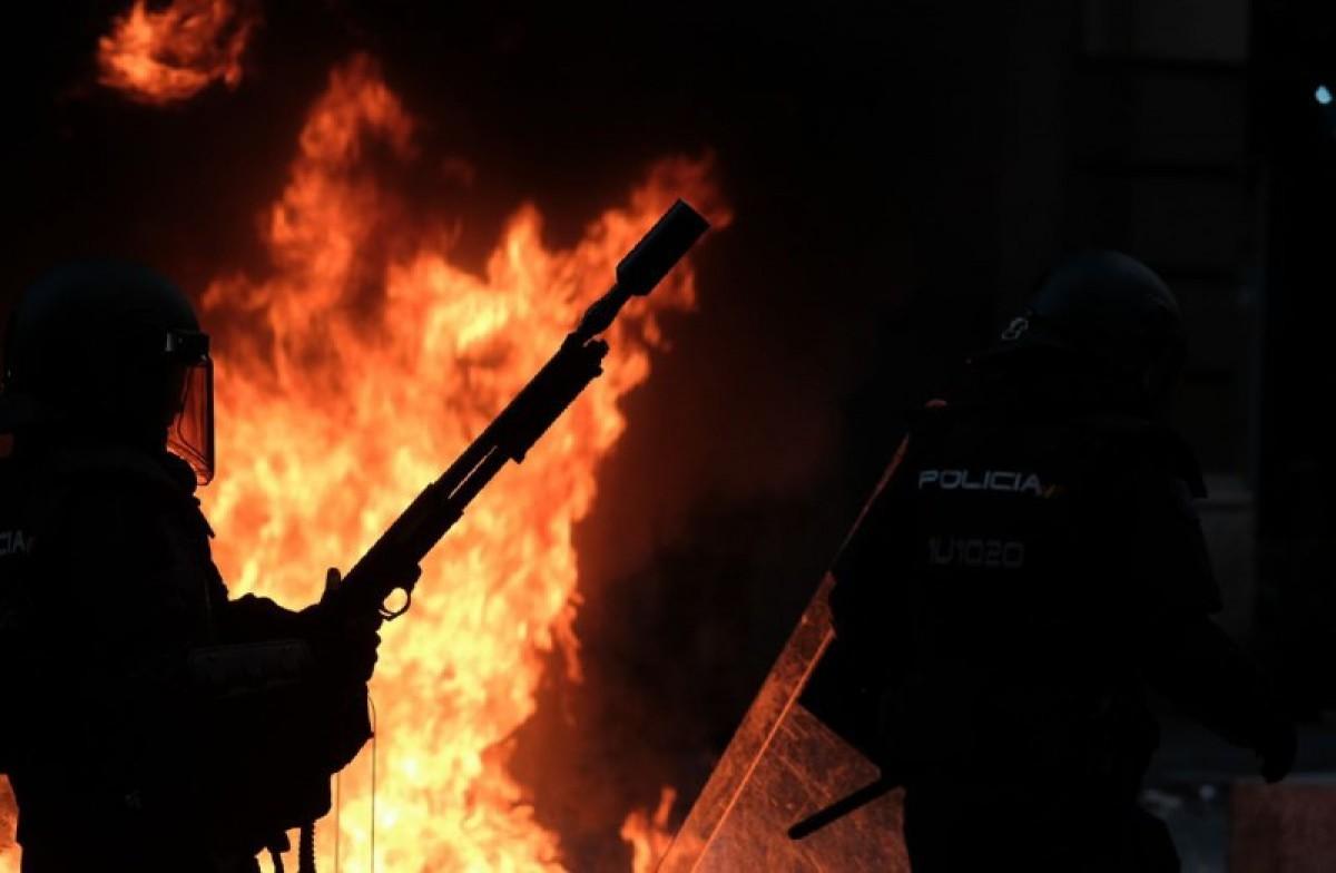 Agents de la Policia Nacional al davant d'una barricada amb foc