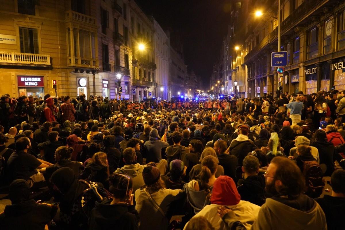 Manifestants a la plaça Urquinaona amb el cordó policial al fons