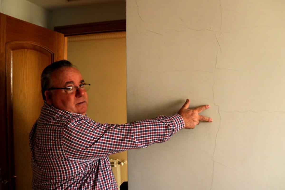 Un veí ensenya les esquerdes provocades pels sismes