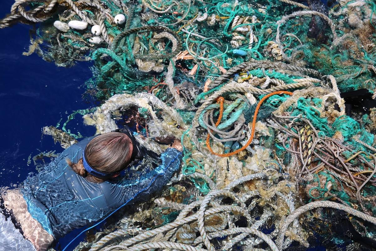 Una dona recollint mostres de plàstic al mar