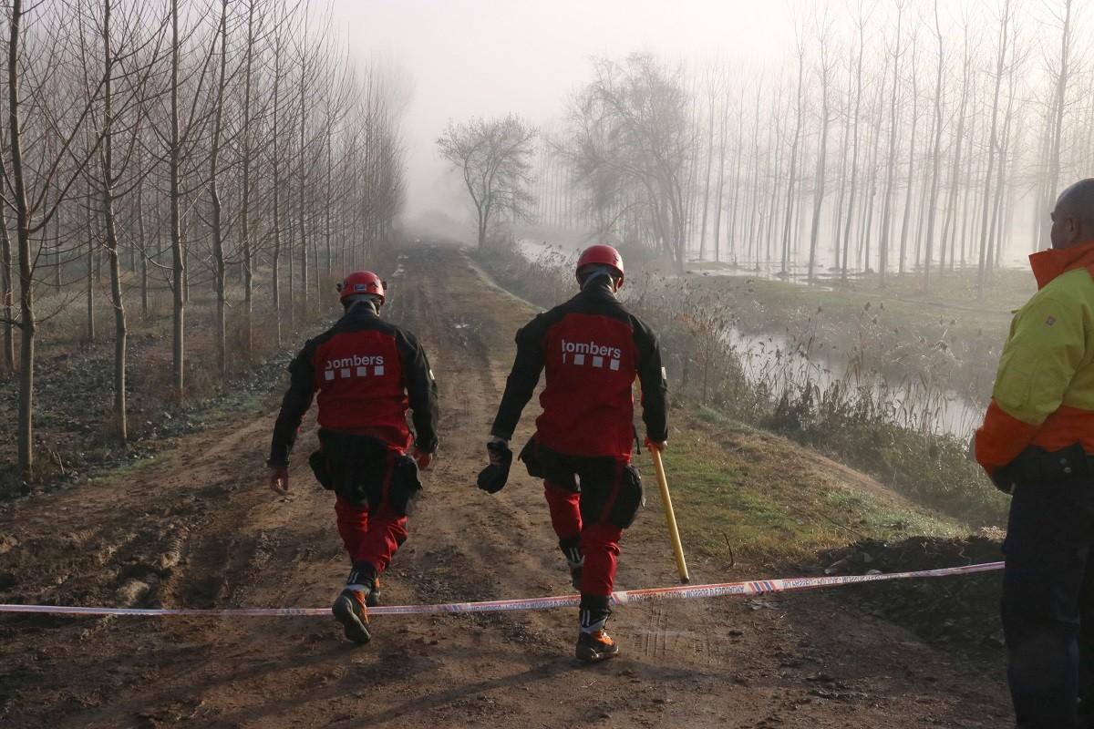 Dos Bombers accedint a la zona de recerca a Sils aquest dissabte