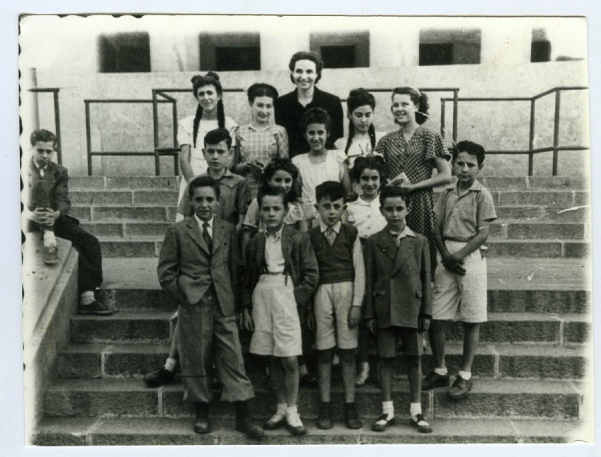 Fotografia de l'Adelita Barberà amb els seus alumnes a la Plaça d'Espanya el juny de 1948.