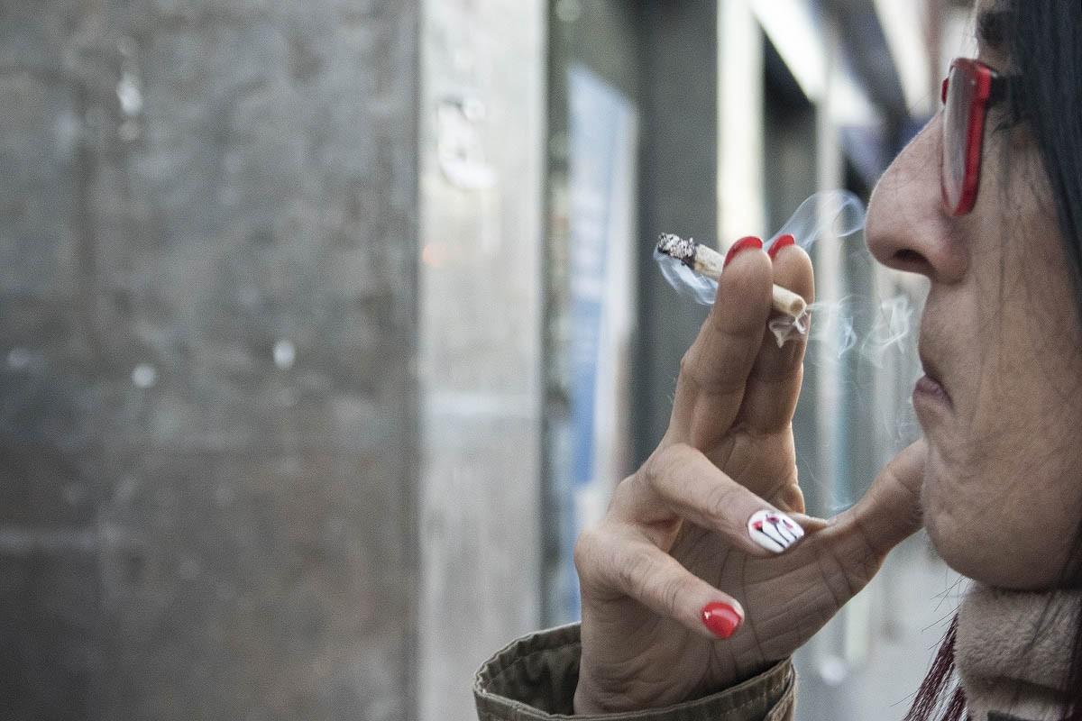 Una senyora fumant al carrer.