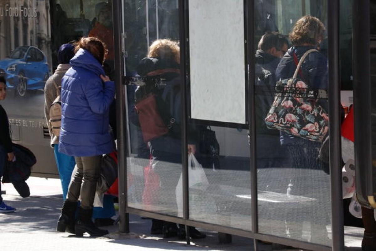 Gent protegint-se del vent, en una parada d'autobús a Valls