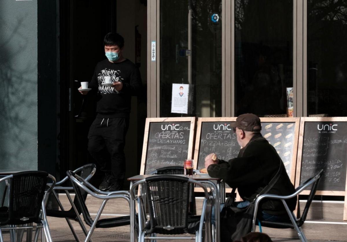 El cambrer d'un bar amb una mascareta com a mesura de precaució pel coronavirus