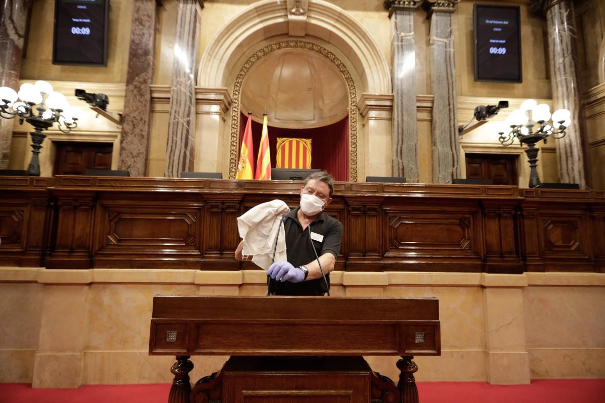 Un treballador del Parlament neteja el faristol.