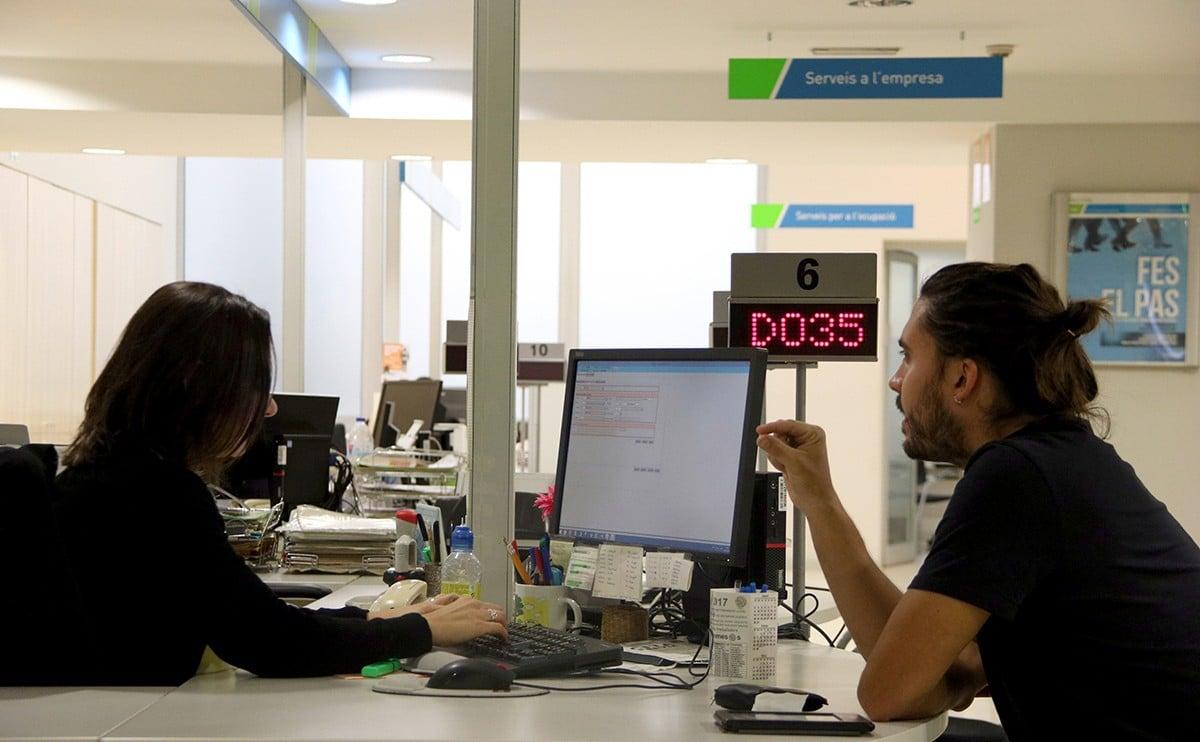 Una treballadora del SOC i un usuari, en una imatge d'arxiu