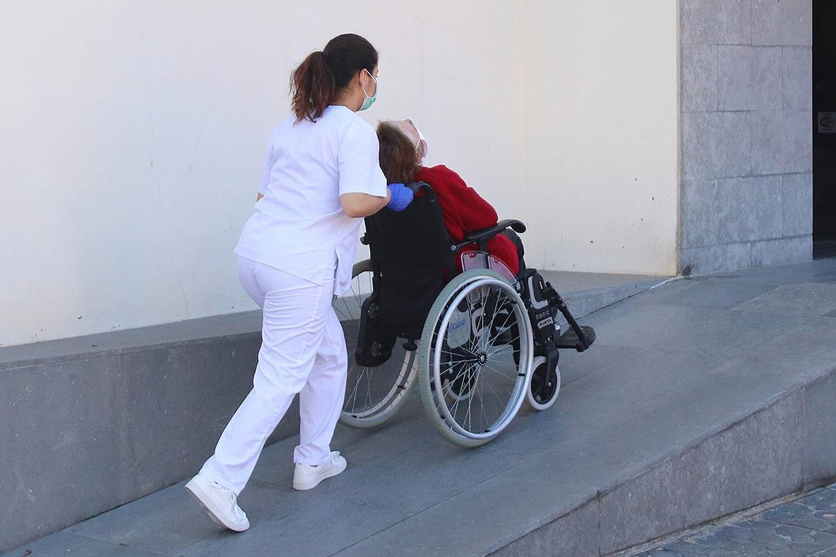 Personal sanitari traslladant una persona gran en cadira de rodes