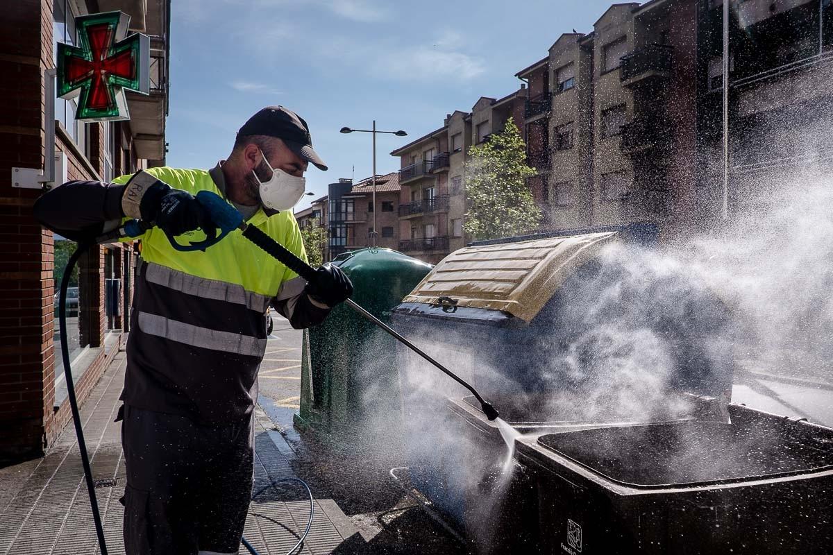 Un operari desinfectant els contenidors en plena pandèmia