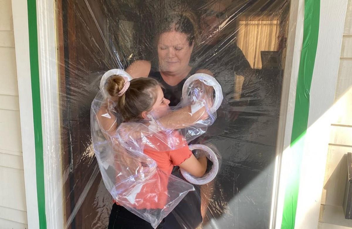 La neta, abraçant la seva àvia amb l'avi al fons