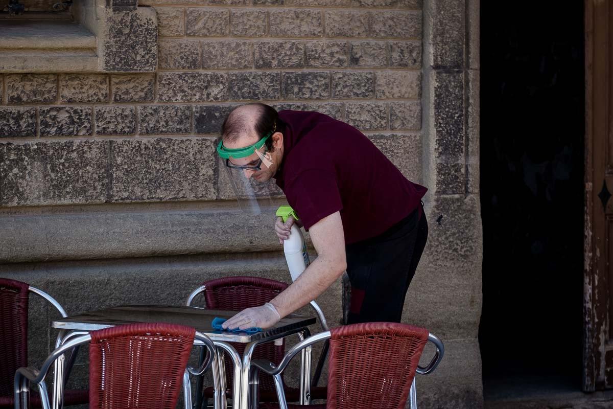 Un cambrer, amb una pantalla facial, desinfecta una taula de la terrassa.