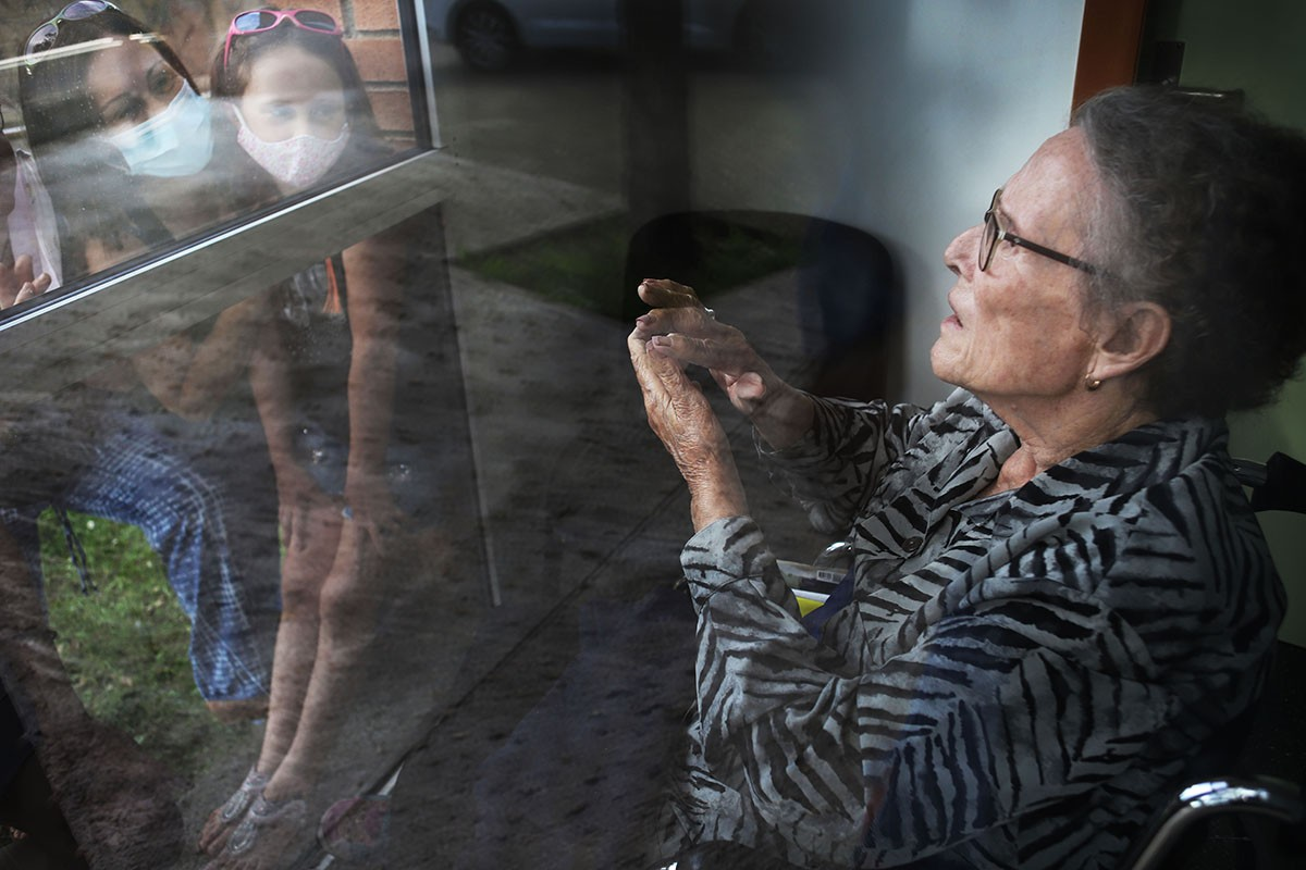 Una resident saludant els seus familiars a través del vidre