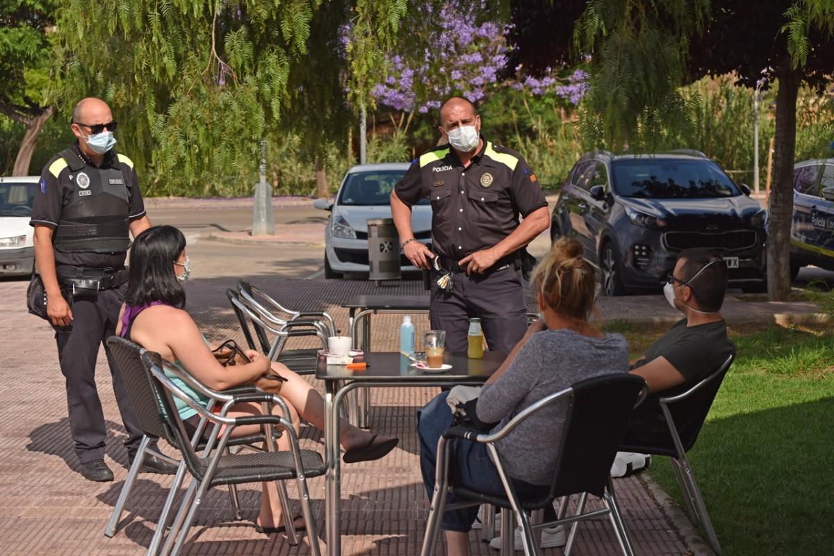 Agents de la Policia Local de la Ràpita informant els clients de la terrassa d'un bar