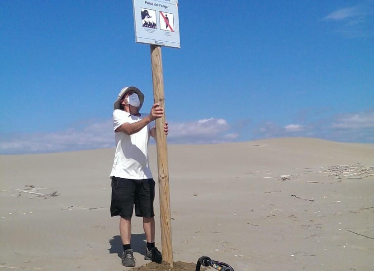 Un operari del Parc col·loca un cartell informatiu