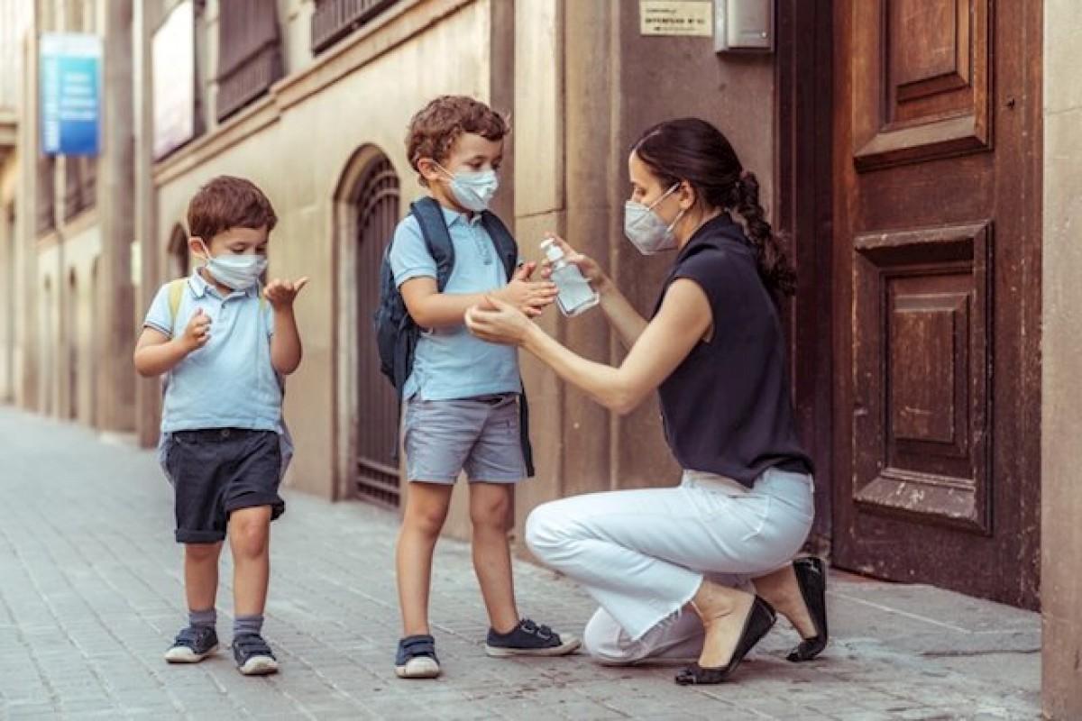 Una mare posant gel hidroalcohòlic als seus fills